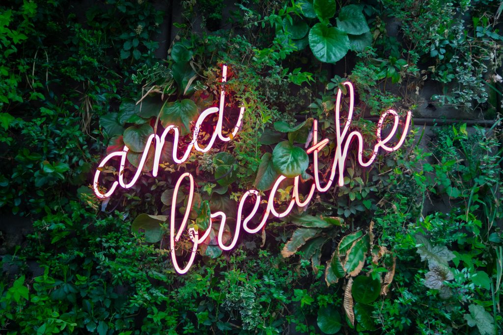 """A neon sign with the words """"and breathe."""""""