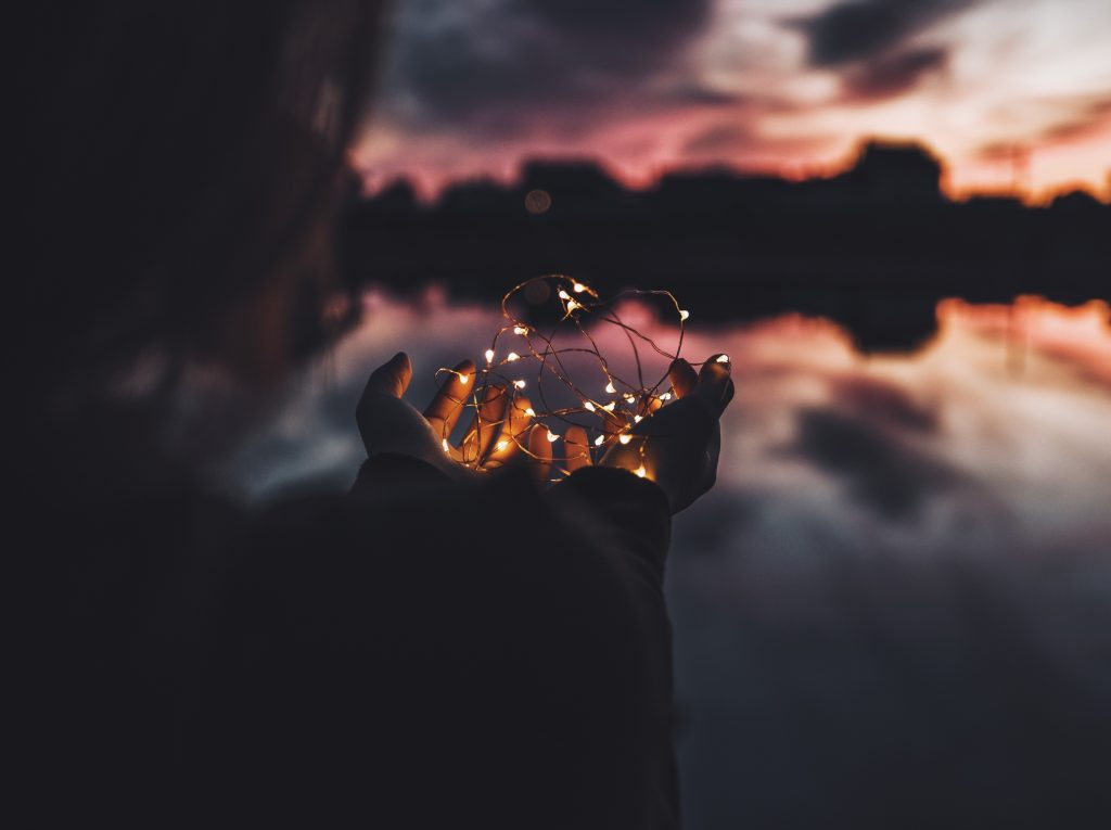 woman's hands holding lights shaped like a heart