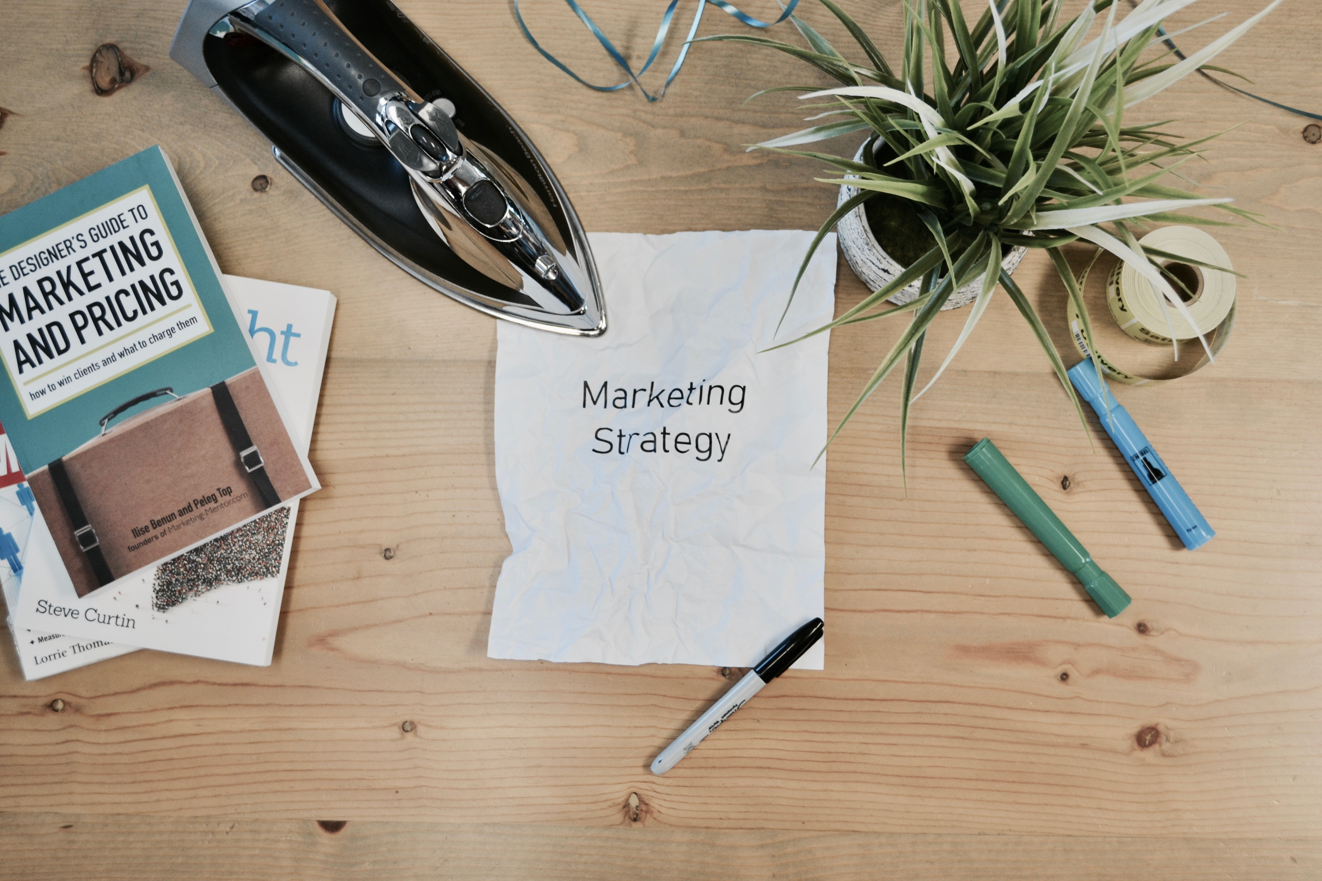 """Picture of a crumpled up piece of paper with the words, """"Marketing Strategy"""" on it."""