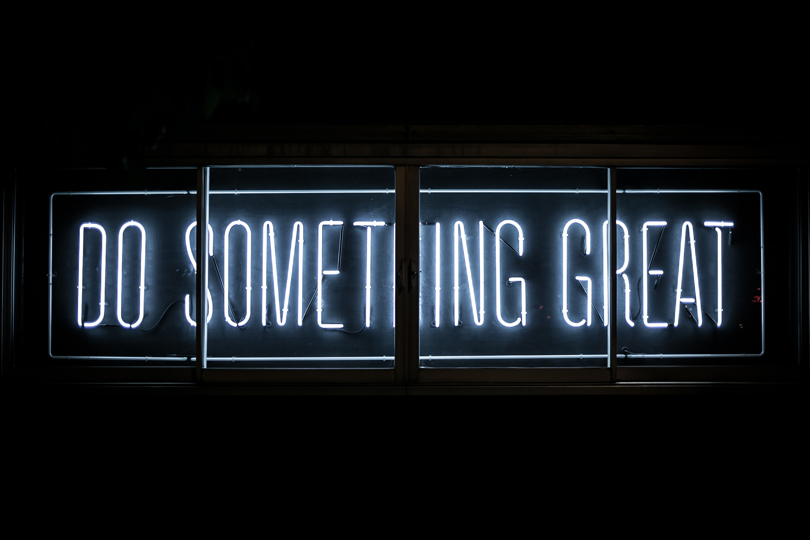 """Picture of a neon sign that says """"Do something great."""""""