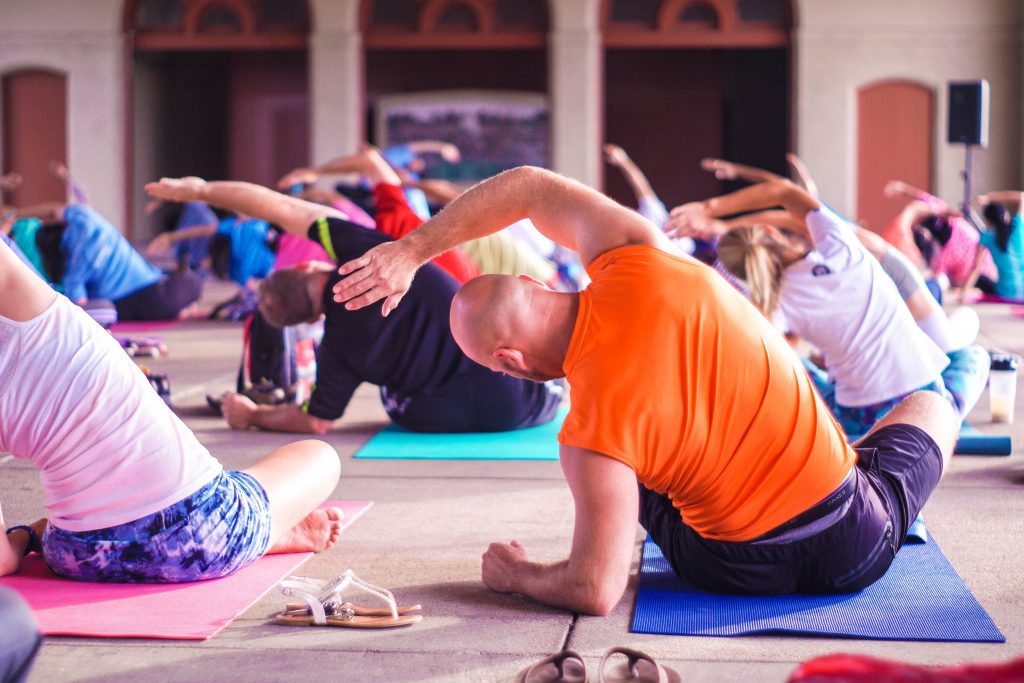 Picture of people in a yoga class doing a side stretch to relieve lower back pain