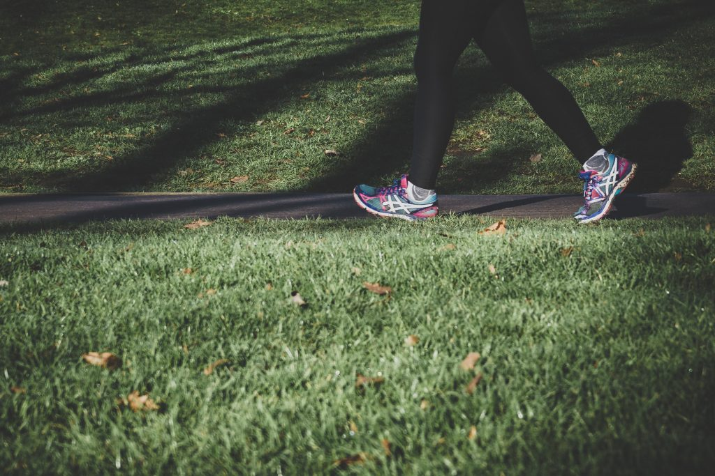 Picture of a women walking in a park with running shoes on